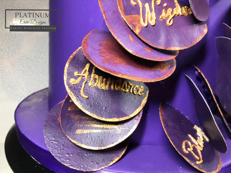 Closeup:  Double barrel birthday cake topped with a sugar placque and covered in purple fondant and edible inspirational words envelop the cake.  Created by Platunum Cake Designs in our Decatur, Ga studio.  Making Memories Sweeter #platinumcakedesigns #decatur #fondant #sugarplacque #purple #inspirational #birthdaycake #inspirational
