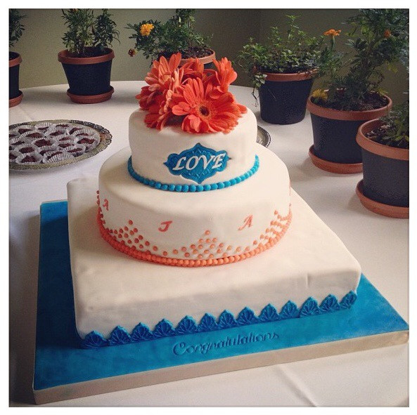 My sister's wedding cake which is mostly white with blue and orange decorations