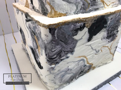Closeup of marbled tier: All buttercream 3-tiered square wedding cake with an all white tier and 2 marbled black, gold, white, and silver tiers.  Handpainted gold and silver highlights.  Created by Platunum Cake Designs in our Decatur, Ga studio.  Making Memories Sweeter #platinumcakedesigns #tieredcake #wedding #marbledbuttercream #decatur #atlanta #blackandwhite #squarecake