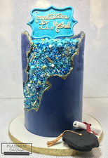 This is a beautiful blue and teal all-buttercream, double barrel, graduation cake adorned with sprinkles with a hand-painted faultline. Created by Platinum Cake Designs in Decatur, GA.  #platinumcakedesigns #buttercreamcake #graduationcake #decatur #atlanta