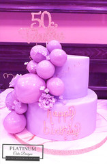 A purple tiered 50th birthday cake covered in fondant and has cascading edible balloons and sugar flowers.  Created by Platunum Cake Designs in our Decatur, Ga studio.  Making Memories Sweeter #platinumcakedesigns #decatur #fondant #50thbirthday #birthdaycake #tieredcake #purple
