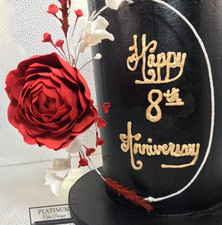 Closeup:  AAll black buttercream cake with red and white sugar flowers and a red sugar peony on a floral wreath  large red sugar peony.  The colors represent the Trinidadian flag.  Created by Platunum Cake Designs in our Decatur, Ga studio.  Making Memories Sweeter #platinumcakedesigns #decatur #fondant #wedding #anniversary #flowerhoop #doublebarrel #trinicake #floralhoop