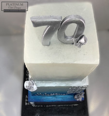 Closeup top view: 3-tiered 70th birthday cake celebrating the important milestones in the celebrants life. Created by Platunum Cake Designs in our Decatur, Ga studio.  Making Memories Sweeter  #70thbirthday #birthdaycake #platinumcakedesigns #decatur