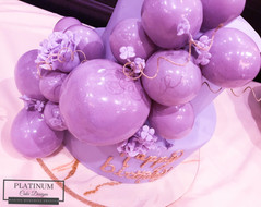 Closeup of balloons and flowers: A purple tiered 50th birthday cake covered in fondant and has cascading edible balloons and sugar flowers.  Created by Platunum Cake Designs in our Decatur, Ga studio.  Making Memories Sweeter #platinumcakedesigns #decatur #fondant #50thbirthday #birthdaycake #tieredcake #purple