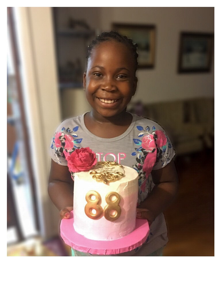 My niece holding her great grandmother's cake which is an ombre buttercream cake with gold accents and large bright pink flower.
