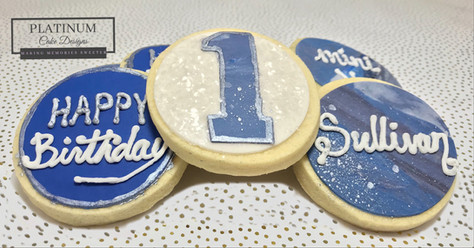 Custom sugar cookies created by Platinum Cake Designs in Decatur, GA to celebrate the 1st birthday for a baby boy who's out of this world.  #makingmemoriessweeter #platinumcakedesigns #customcookies #sugarcookies #bluecookies #decatur #atlanta #1stbirthday #galaxy #outerspace