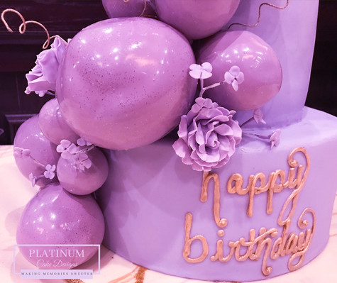 Closeup of balloons: A purple tiered 50th birthday cake covered in fondant and has cascading edible balloons and sugar flowers.  Created by Platunum Cake Designs in our Decatur, Ga studio.  Making Memories Sweeter #platinumcakedesigns #decatur #fondant #50thbirthday #birthdaycake #tieredcake #purple
