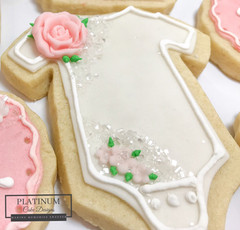 Closeup:  Baby shower cookies for an expectant mother and her baby girl.  #sugarcookies #babygirl #babyshower #decatur #atlanta #onesie #makingmemoriessweeter #platinumcakedesigns