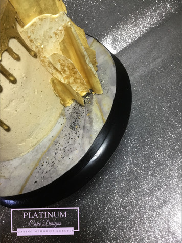 Closeup: Off-white all buttercream cake with hand painted gold drip and gold chocolate sails and marbled fondant baseboard.   Created by Platunum Cake Designs in our Decatur, Ga studio.  Making Memories Sweeter #platinumcakedesigns #decatur #buttercream #birthday #chocolatesails #gold #singletier #atlanta