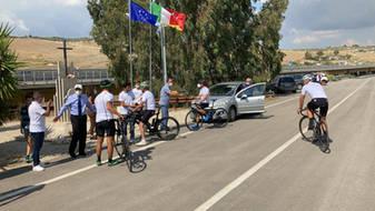 I ciclisti in arrivo da Regalbuto sostano con il Mattone del mondo per l'Italia sulla strada statale 640 dove venne ucciso il 21 settembre 1990 il giudice Rosario Livatino.
