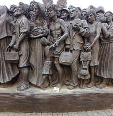 Il mattone posto accanto al monumento al Migrante in Piazza San Pietro, scultura realizzata dall'artista canadese Timothy Schmalz.