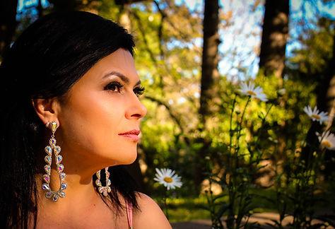Olhos Encantados, Paola Moreira, fotógrafa em Porto Alegre. Parque Alim Pedro, IAPI. Mulher maquiada com brincos grandes e margaridas ao fundo.