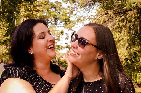 Olhos Encantados, Paola Moreira, fotógrafa em Porto Alegre. Fotos em hotel em Gramado. Casal de mulheres brancas de cabelos lisos, blusas pretas com petit poa, segurando as mãos. A mulher da esquerda faz carinho no rosto da mulher à direita.