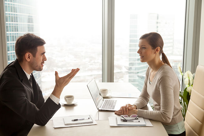 businessman-and-businesswoman-discussing-work-at-office-desk.jpg
