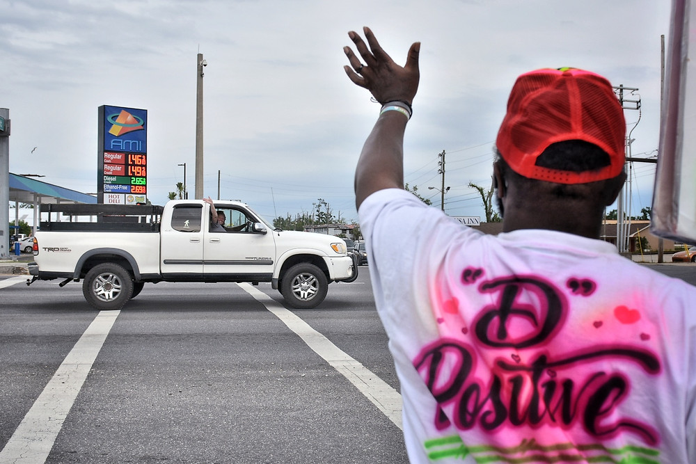 A passing motorist waves back at Decaris Hunter, April 15th, 2020, Panama City, Fl. (Photo by Dylan Gentile)