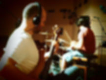 bassist and drummer recording a song
