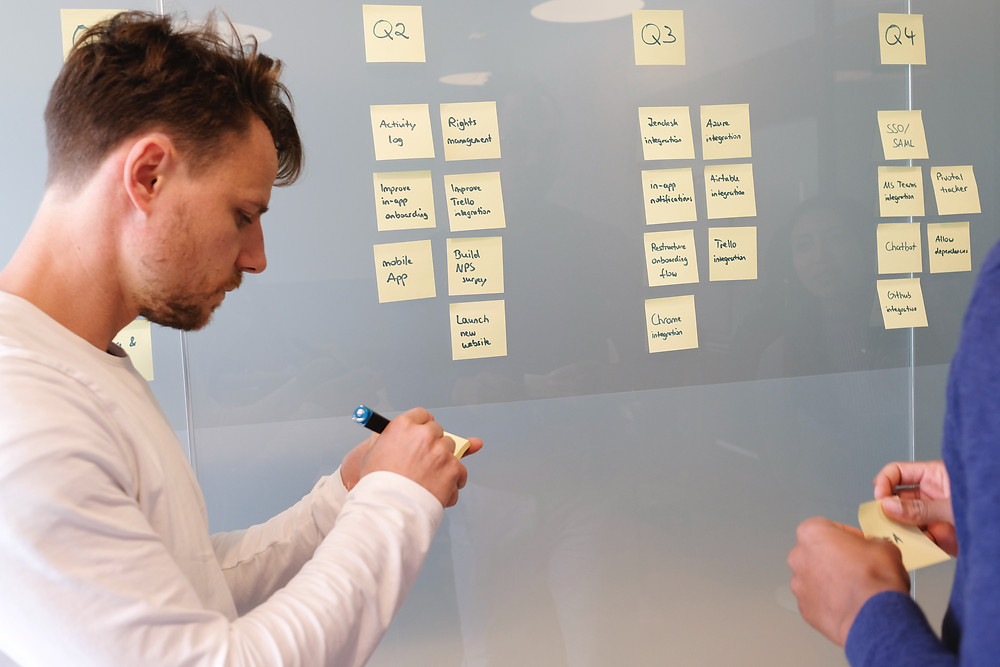 man writing sticky note to help plan for tender writing