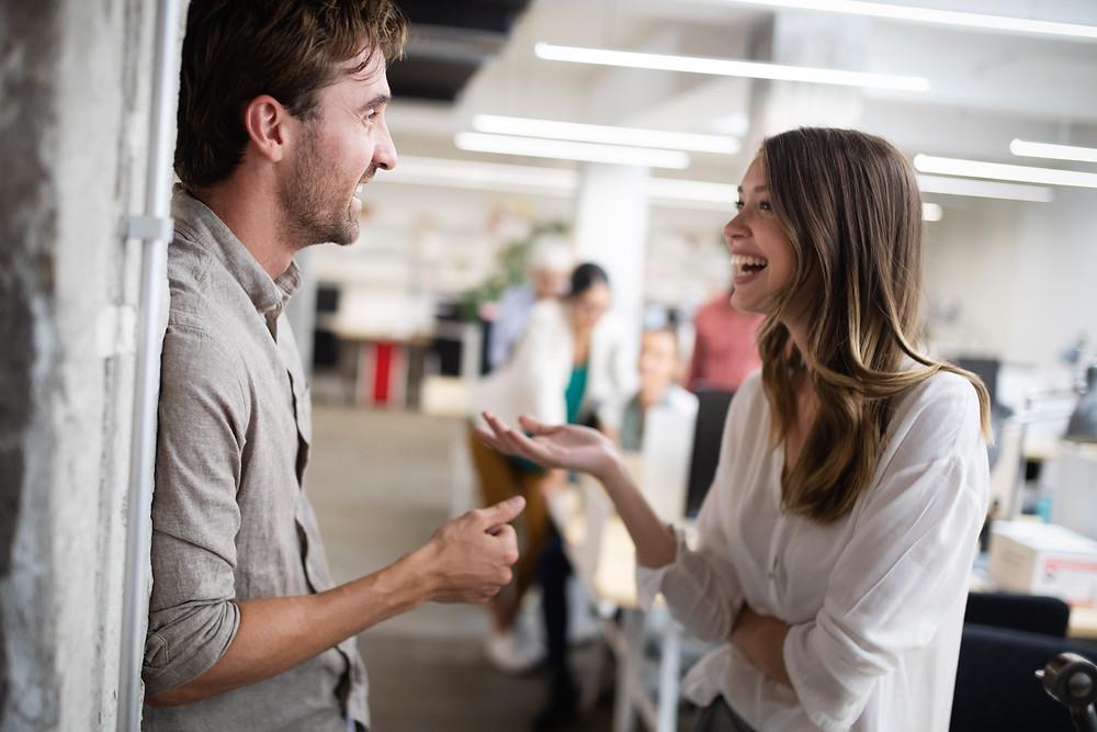 Zwei lachende Menschen unterhalten sich im Büro