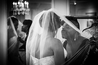 Bride and her mother getting ready and sharing a kiss.
