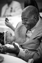 Elderly man and young child sharing a moment at a wedding reception.