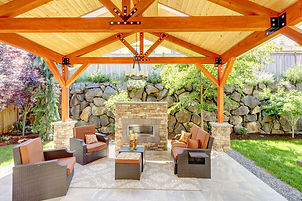 beautiful and airy covered patio with stone fireplace and rock wall