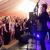 Band performing on a stage using hired pa system for the event