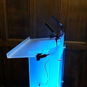 Illuminated blue acrylic lectern at pembroke college with mics
