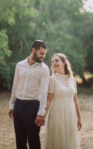"""Noam: """"I came to Omri several months before my wedding, in order to find a second dress. I sewed the first dress at a designer, and I was looking for another dress for the dancing part of the wedding. I arranged with Omri for a day, were we will search for a suitable dress. This day turned out to be both effective and fun! Omri managed to understand my personal taste and at the same time, to take into account quite a few parameters I had such as, modesty, budget, comfort, etc. On the wedding day I enjoyed a beautiful and comfortable dress which also served me for our couple photos."""""""