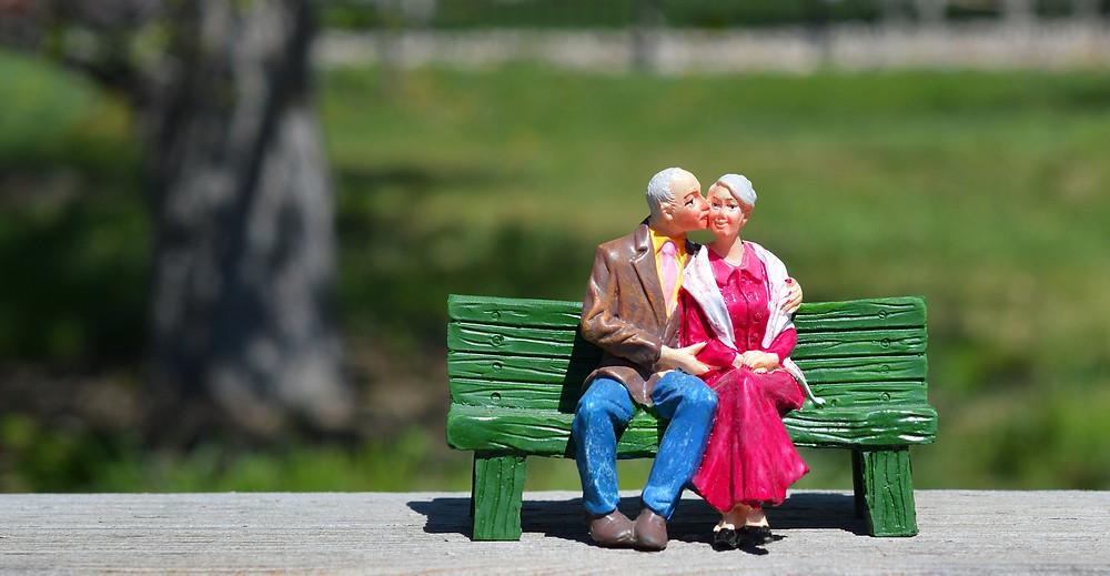 בובות חרס של זוג מבוגרים יושבים על ספסל ירוק הגבר נושק לאישה בלחיה
