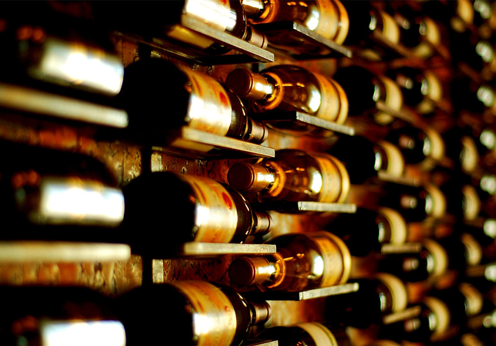 A foto showing Italian wine bottles , one of the most popular italian products, the bottles are light yellow in a winery cellar.