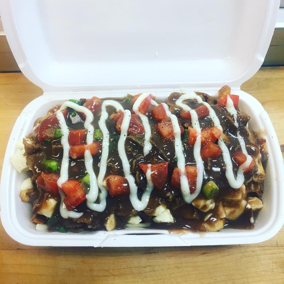 Poutine in takeout container. Multiple toppings