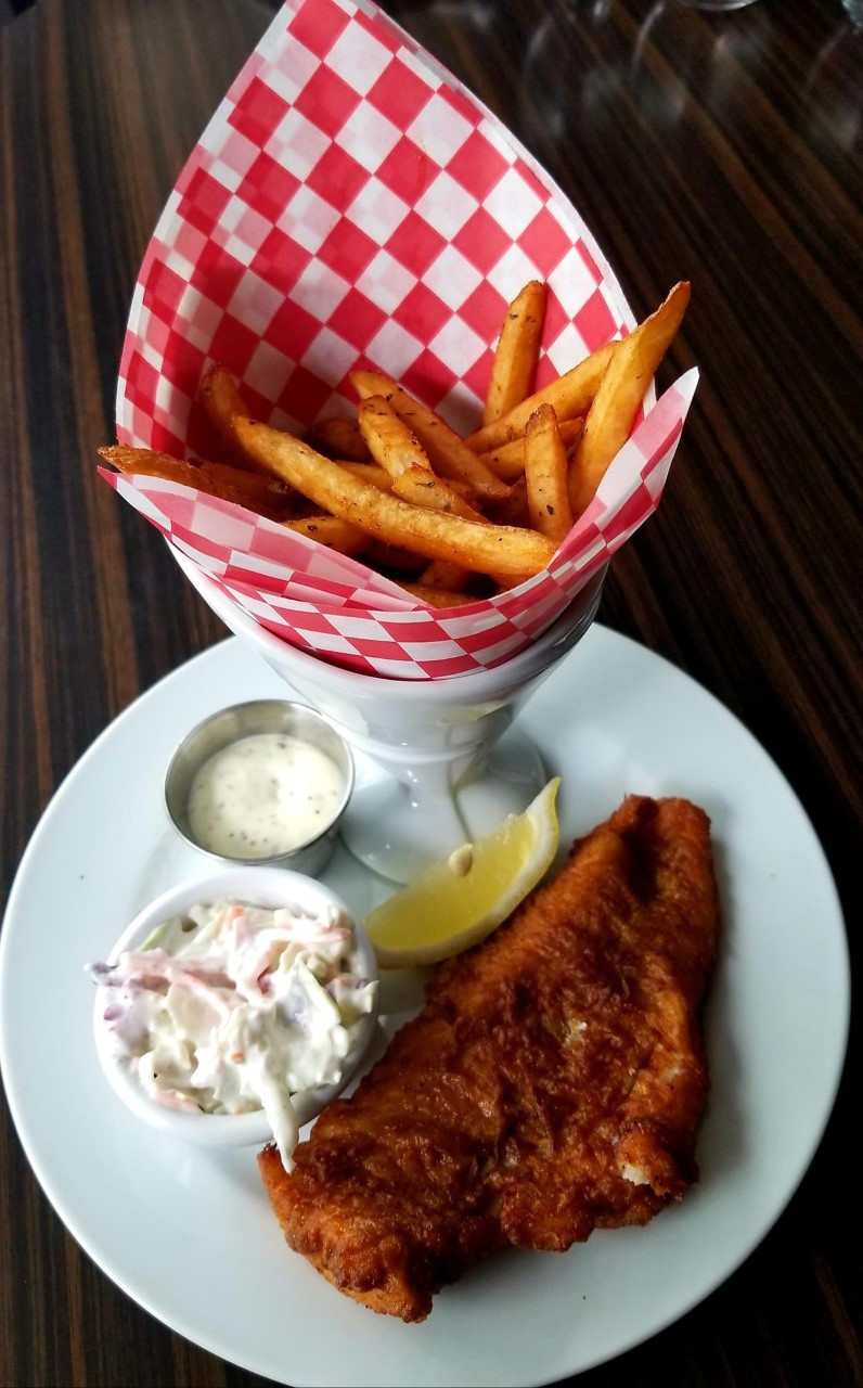 Fish and chips plate. Fries in paper cone, fried fish, coleslaw