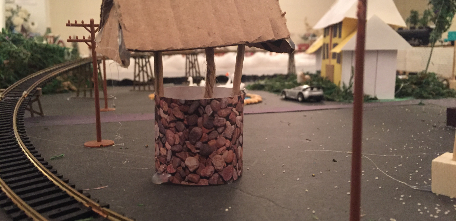 "Used stonelike designer paper, mini wooden dowels, cardboard and rope in the center of the ""well."""
