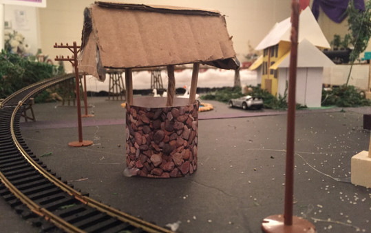 """Used stonelike designer paper, mini wooden dowels, cardboard and rope in the center of the """"well."""""""