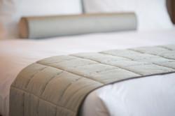 close-up-de-la-couverture-grise-sur-le-lit_1122-1470