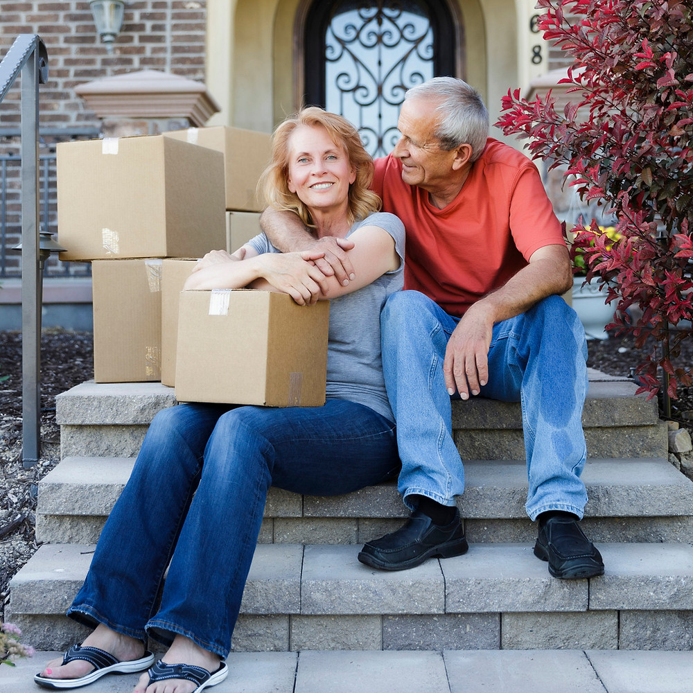 middle-aged-couple-sitting-on-front-steps-with-moving-boxes