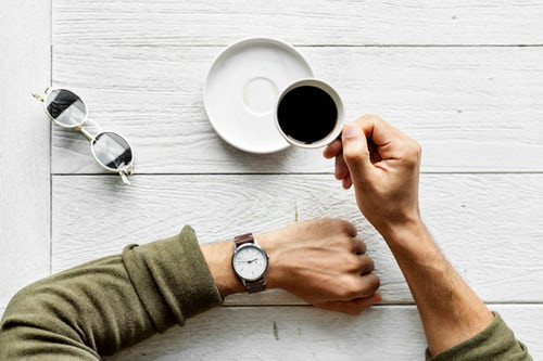 first-person-view-holding-cup-of-coffee-and-checking-wrist-watch