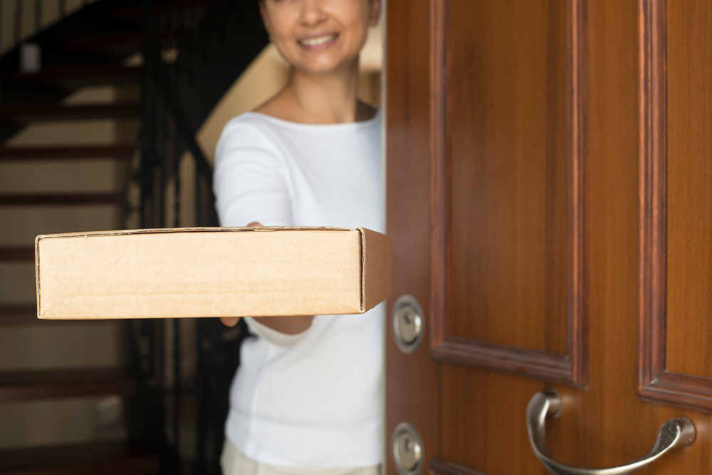 woman-standing-in-doorway-holding-brown-delivery-box