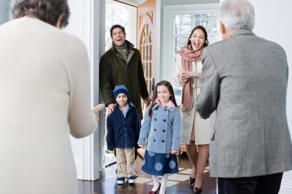 family-with-two-kids-greet-grandparents-in-house