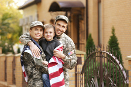 Military family reunited on a sunny day.