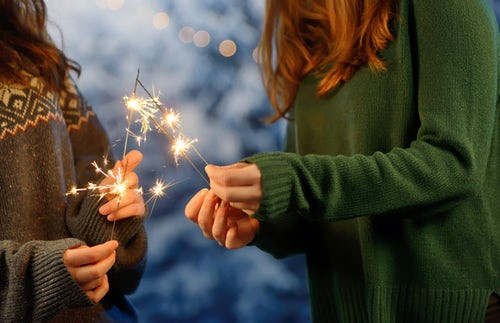 two-women-in-sweaters-holding-sparklers-outside