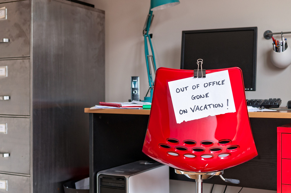 red-desk-chair-with-note-saying-out-of-office-gone-on-vacation
