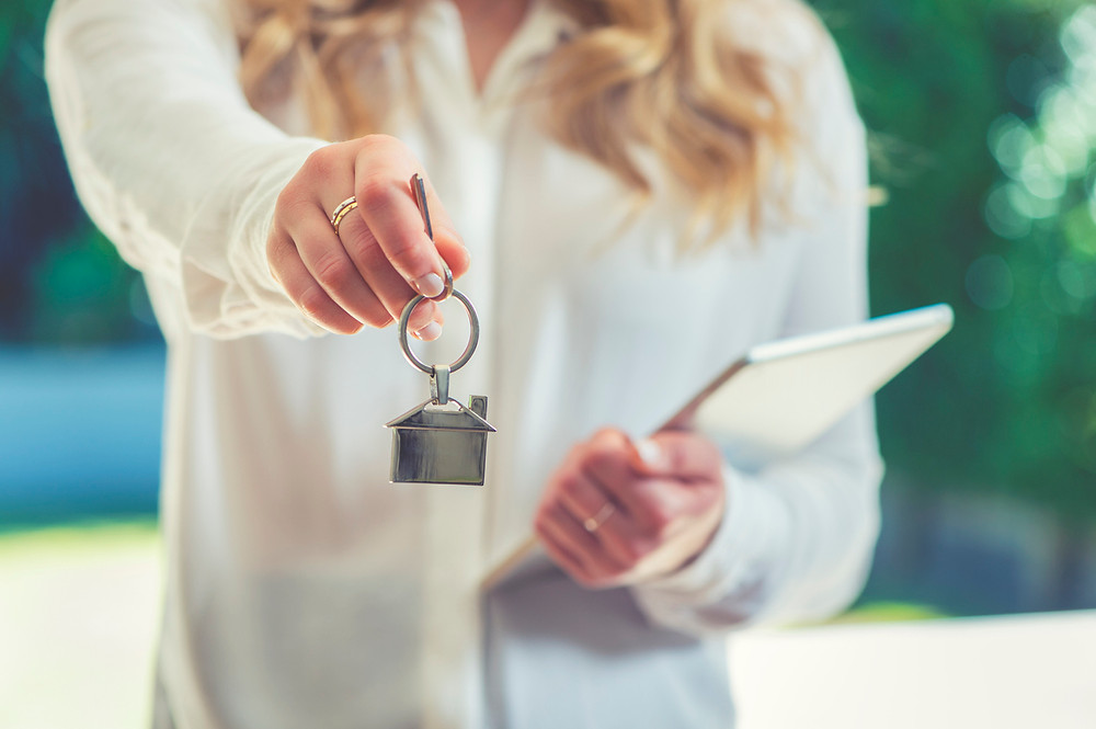 woman-in-white-blouse-handing-keys-to-rental-property
