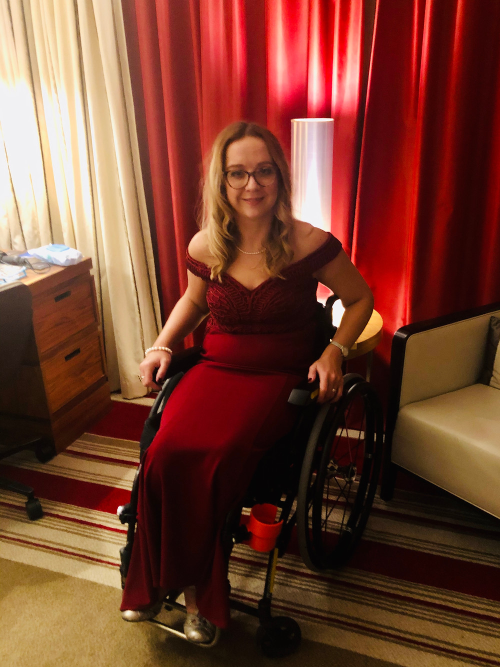 Carrie-Ann sitting in her wheelchair wearing a long red dress