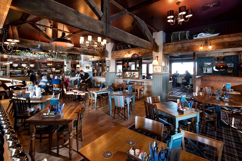 Pub dining room with wooden floors and tables, customers eating meals