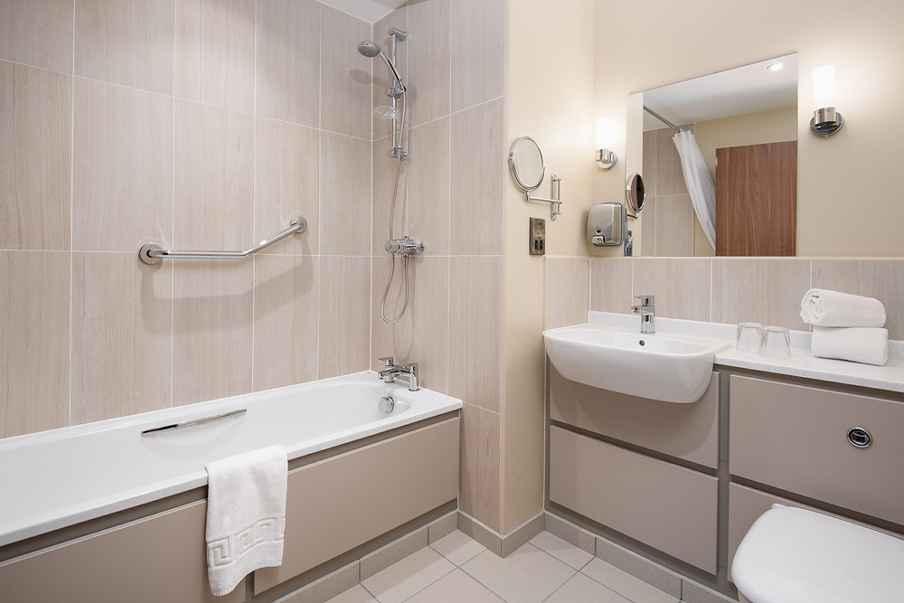 Tiled hotel bathroom with bath tub and sink