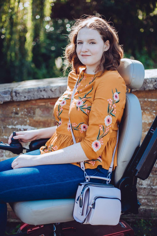 Shona sitting in her powerchair wearing an orange top