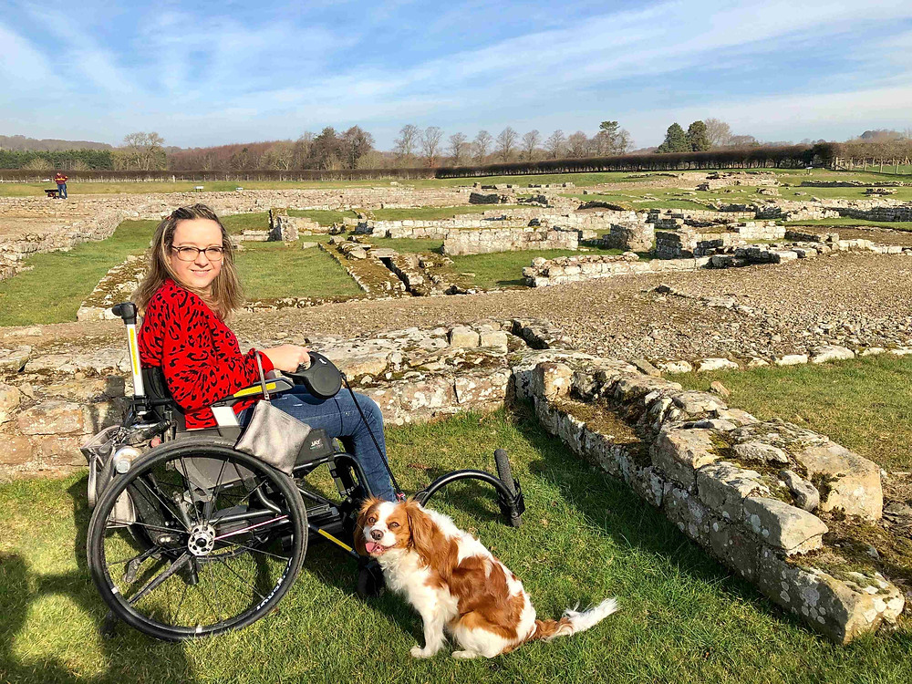 Carrie-Ann Lightley Disabled Travel Blogger with her dog Poppy in front of Corbridge ruins