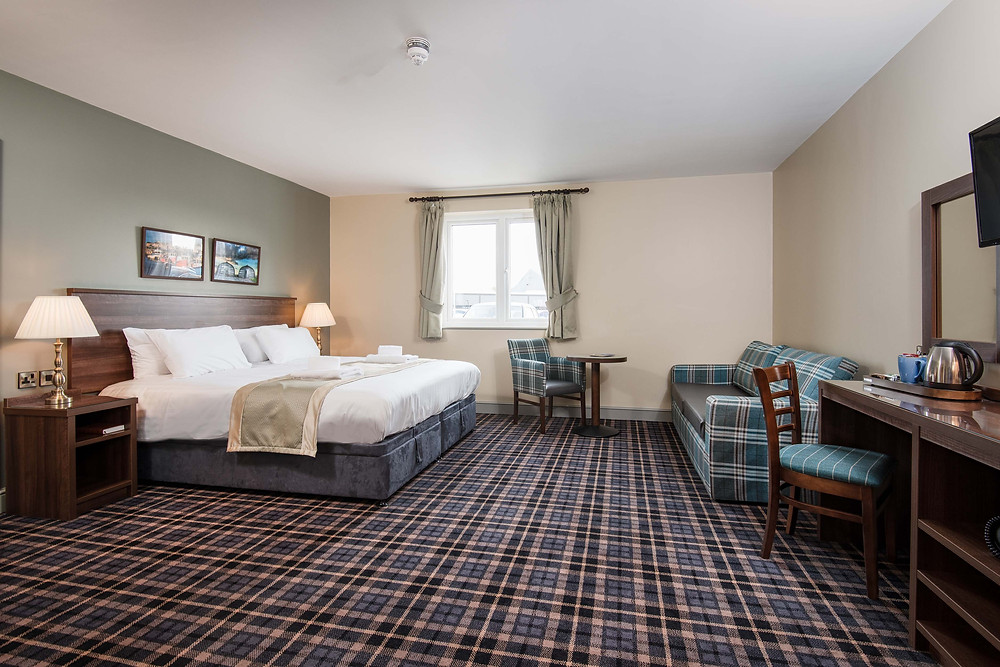 Large hotel bedroom with checked carpet, large bed and wooden desk
