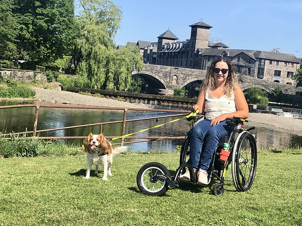 Disabled lockdown holiday at home - wheelchair user Carrie-Ann sitting by a Lake District river, holding her dog on a lead